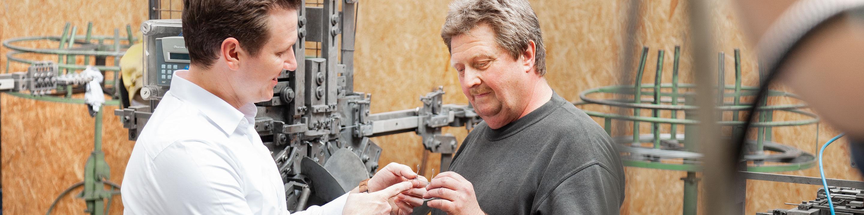 Zwei Fachkräfte inspizieren ein fertiges Drahtstück für den Rollladenbau