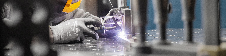 Schweißtechnik: Fachkraft in Schutzkleidung schweißt Metallstücke zu einer Baugruppe