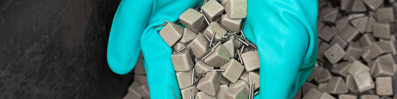 Oberflächentechnik - Hände in blauen Handschuhen halten Poliersteine