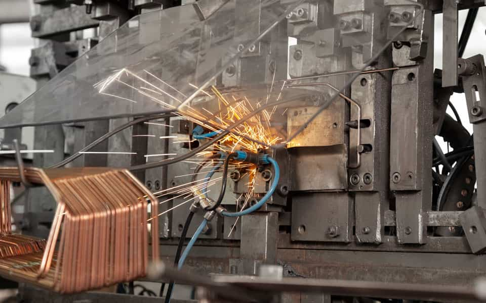 Kupferdraht wird in der Drahtbiegemaschine zu einem Drahtbiegeteil gebogen