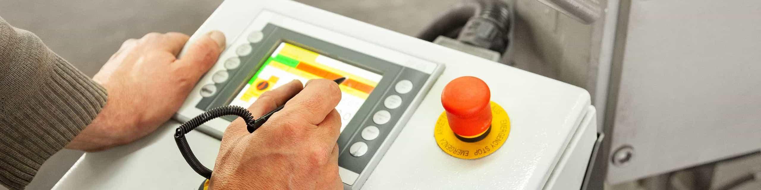 Facharbeiter steuert Bedieneinheit einer Rohrbiegemaschine für die Rohrbiegetechnik