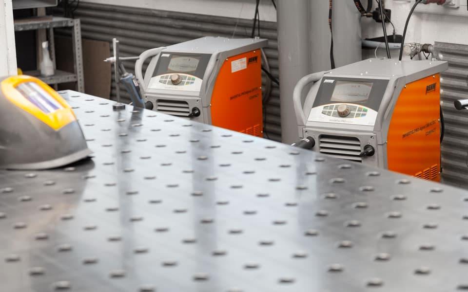 Zwei Rehm WIG-Schutzgas-Schweißgeräte hinter Schweißtisch stehend